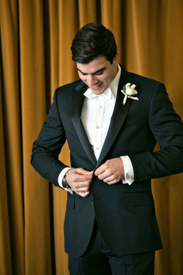 Black tuxedo and white collar bow tie buttons boutonniere buttoning jacket