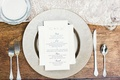 Ranch wedding reception wood table with silver charger and reception program with couple's monogram