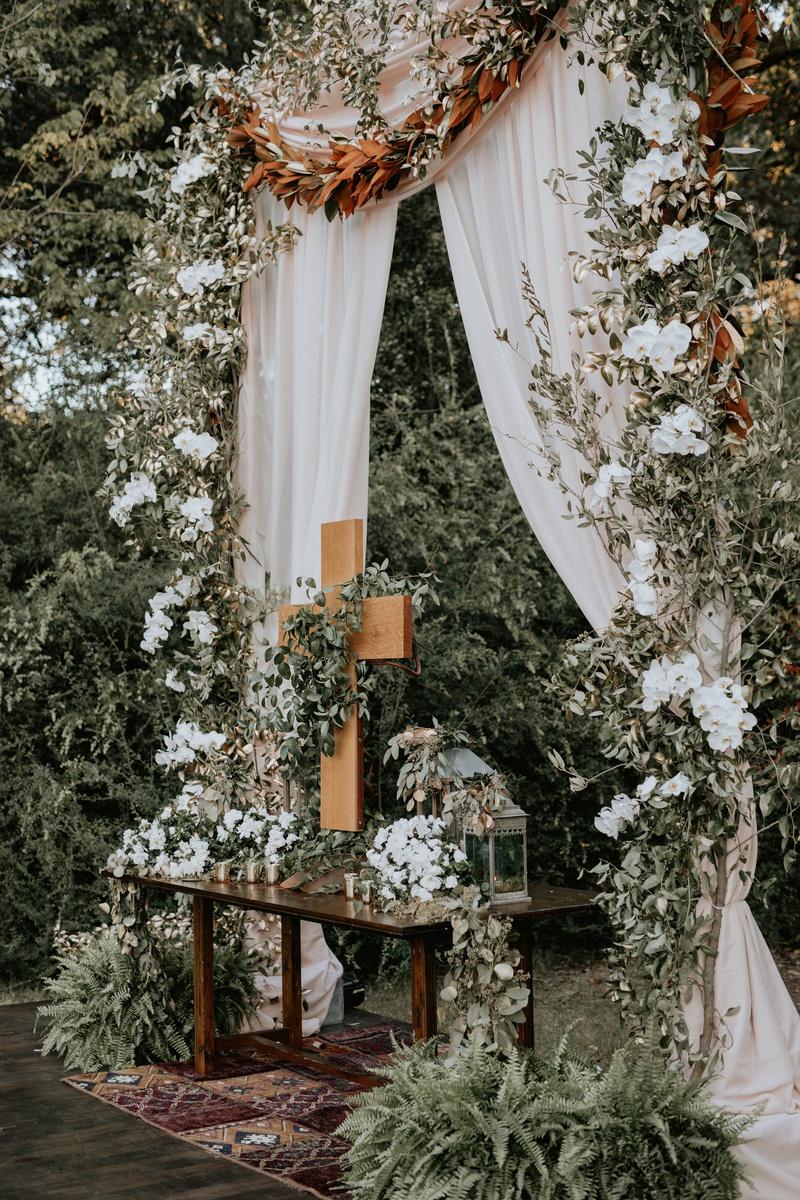 wedding ceremony vintage rug wood table altar cross magnolia greenery burgundy flowers
