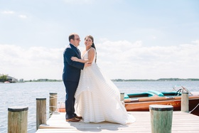 bride in striped hayley paige wedding gown with groom in navy on the private dock