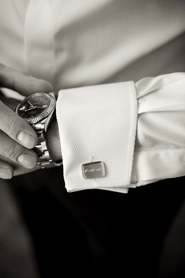 Black and white photo of groom's engraved cuff links and watch white tuxedo button down shirt