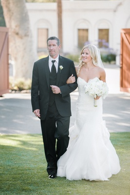 Bride in a strapless Hayley Paige dress and white bouquet walks down the aisle with father