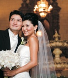 Bride wearing a strapless Vera Wang gown and veil with groom in black tails