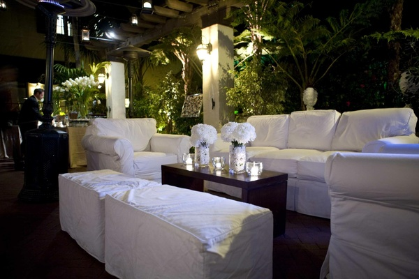 Outdoor lounge area with white sofas and armchairs
