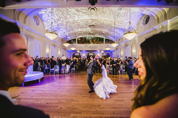 Bride and groom dancing in background of photo
