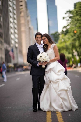 Bride in a Monique Lhuillier gown with a lace bodice and pick-up skirt with groom in a black tuxedo