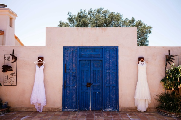 mermaid wedding gowns hang in front of ranch venue