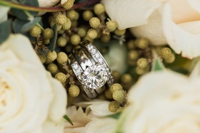 Round-stone engagement ring with a pair of diamond wedding rings in the middle of white roses