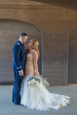 Groom in mess blue uniform and bride in gold dress