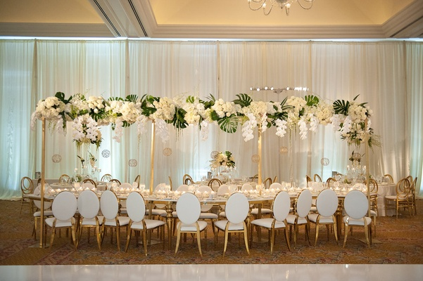 Serpentine table white gold chairs tall centerpiece design of white orchids, roses, monstera leaves