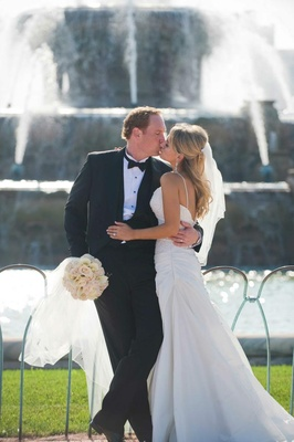 Bride in a spaghetti strap gown with a embroidered bodice kisses groom in a black tuxedo