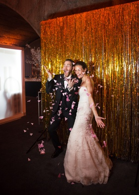 newlyweds strike a silly and playful pose for their photo booth and throw pink flower petals