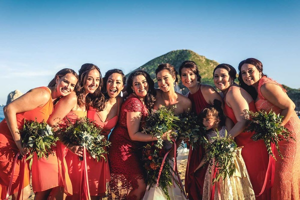 a bride in her white wedding gown standing with her bridesmaids wearing varying coral dresses