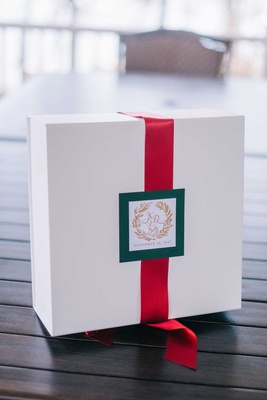 welcome box for holiday wedding white box red ribbon green tag gold monogram