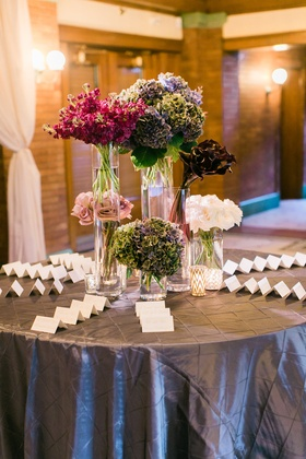 Wedding reception round escort card table with roses, calla lilies, hydrangeas and other flowers