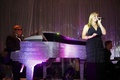 Singer in front of piano with Elton John impersonator
