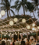 wedding reception outside palm trees string lights gold chameleon chair collection seats dusk shot