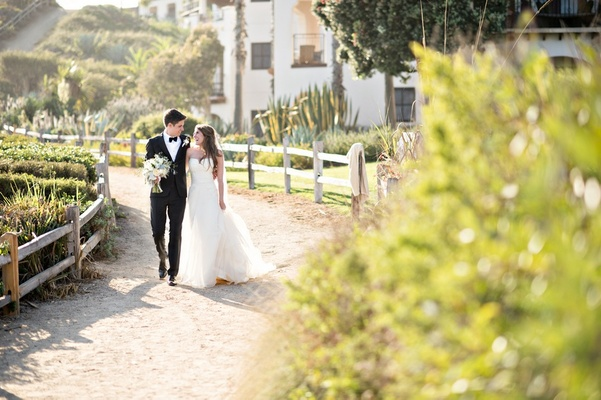 bride and groom stroll and laugh at Bacara Resort wedding
