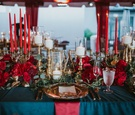 wedding reception navy linens, red tapered candles, scarlet peonies