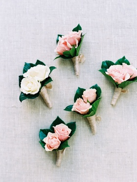 Groom white two flower boutonniere and groomsmen pink boutonnieres two flowers roses