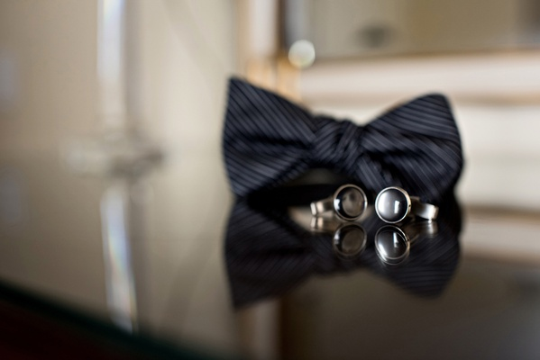 black bow tie with subtle stripes, round black cuff links