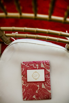 Gold chair topped with paisley ceremony booklet