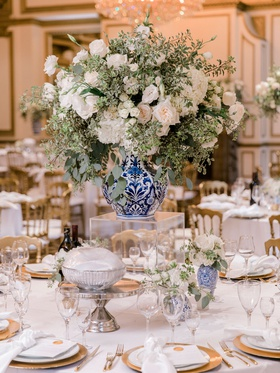 wedding reception centerpiece white flower greenery blue white vase acrylic riser gold details