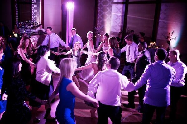 Wedding guests dancing in purple lighting