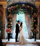 Bride and groom kiss under branchy ceremony structure