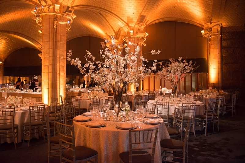 a reception space with circular tables featuring white table linens and bright uplighting