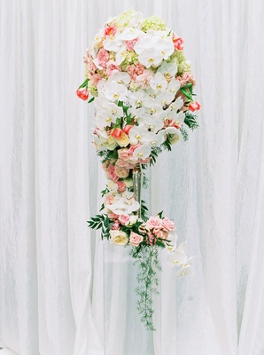 tall ceremony floral arrangement white orchids blush flowers leafy greenery white backdrop