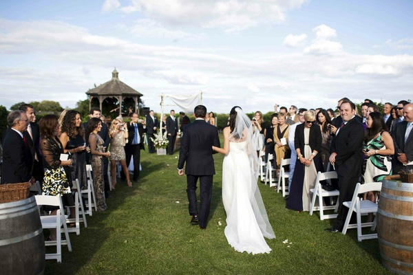 Alfresco wedding ceremony next to wine barrels