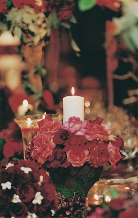 Mossy vase with red roses and white pillar candle