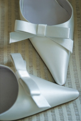 Pointy white satin bridal heels with bow detail