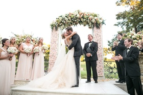 Couple kisses after exchanging vows under floral arch at ceremony