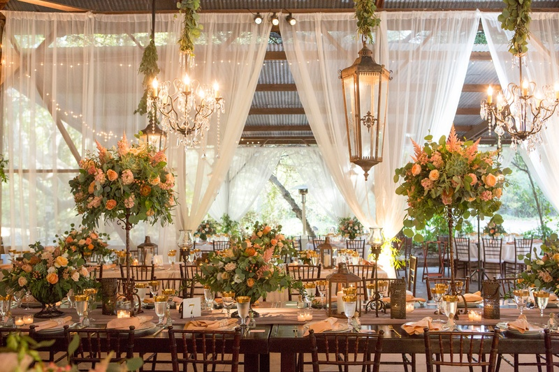 Wedding reception long wood table high low centerpiece chandeliers green garlands drapery rafters