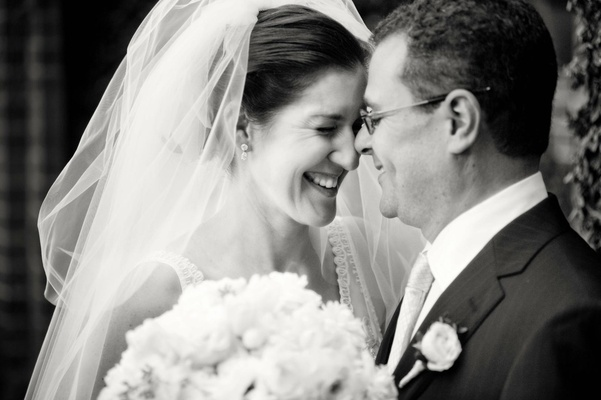 Black and white image of bride and groom touching foreheads