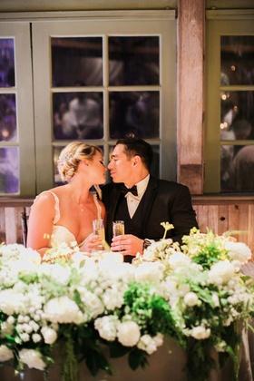 bride in galia lahav groom in men's wearhouse about to kiss sweetheart table wedding toasts