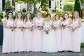 Bride with seven bridesmaids pale pink gowns mismatched necklines matching bouquets greenery crowns