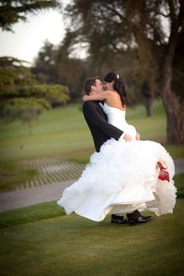 Groom in black tuxedo hugs bride in a Maggie Sottero dress with ruffled skirt