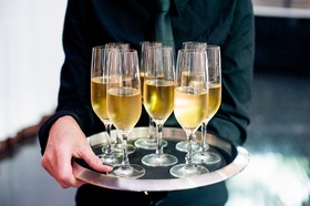 Wedding reception cocktail hour server in black shirt and tie holding tray silver rim champagne