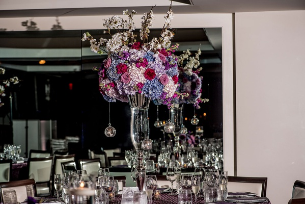 tall centerpiece with blue and white hydrangeas, burgundy roses, taller white flowers