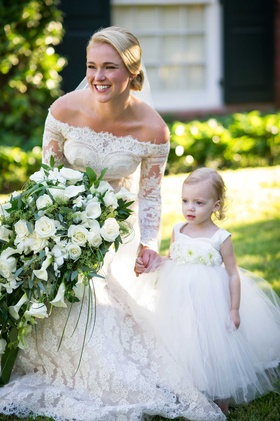 Bride in off the shoulder long sleeve lace Isabelle Armstrong wedding dress with flower girl