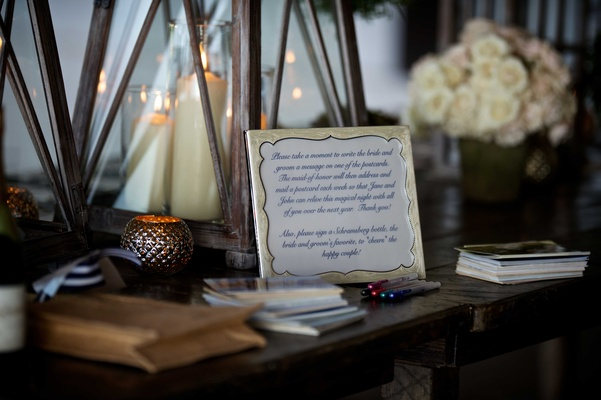 Wedding reception table with instructions to write a message for the bride & groom on postcards