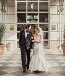 Bride in strapless mermaid wedding dress sweetheart neckline groom in suit and bow tie checker floor