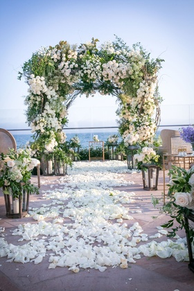 Wedding ceremony ocean view Santa Barbara greenery white flower arch chuppah lanterns flower petals