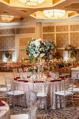 wedding reception gold ballroom round table burgundy napkin tall centerpieces nuage designs