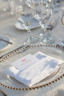 Beach wedding reception place setting with clear charger, seating card with pink starfish