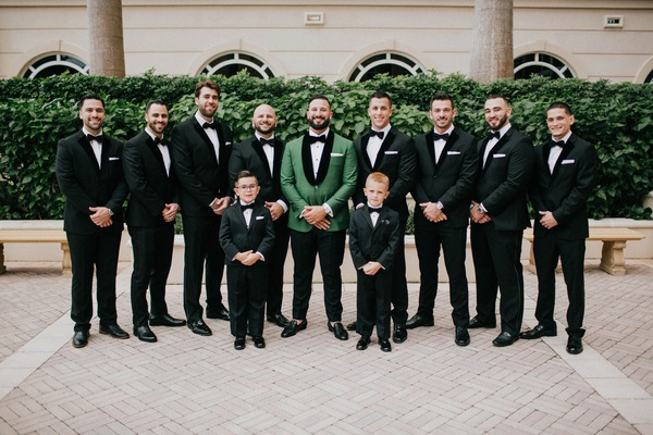 groom in emerald green tuxedo jacket bow tie groomsmen in velvet tux and ring bearers