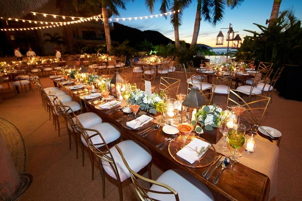 Long wood reception table with twinkle lights and ocean view